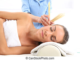 Ear candling - Woman relaxes in the study of natural...