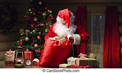 Hit the Road - Santa Claus packing gift boxes in sack and...