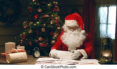 Short of Time - Close up of Santa Claus skimming letters,...