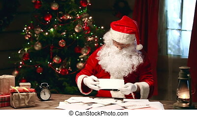 Reading Letters - Santa Claus sitting at the table and...