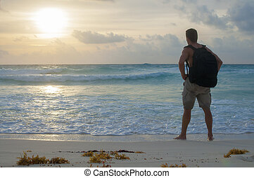 Hiking beach at sunrise - Adventurous Caucasian hiker stands...