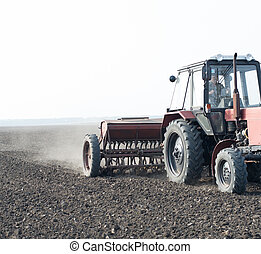 tractor and seeder planting crops on a field - Farmer in...
