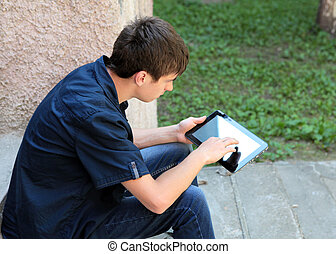 Teenager with Tablet Computer on the landing steps of the...