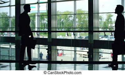 Business Greeting - Silhouettes of two businessmen greeting...