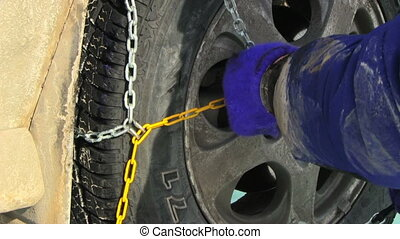 snow chains - Man putting snow chains on tire