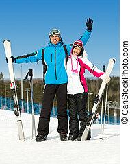 Full-length portrait of hugging skiers - Full-length...