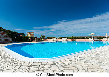 swimming pool with tiled border and turquois water at blue...