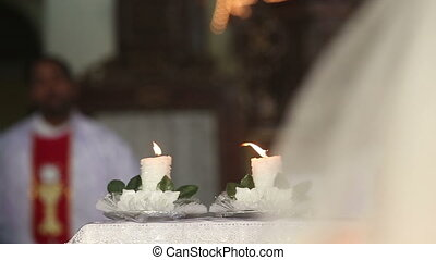 before the bride at the altar candles are lit and priests -...
