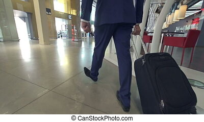 Air Travel - Slow motion of man with luggage walking along...