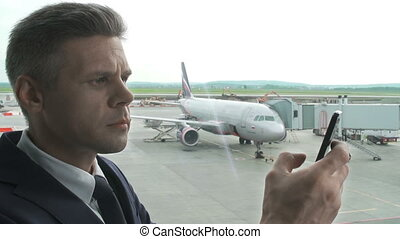 Flight Delay - Close up of businessman making a phone call...