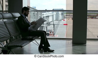 Tedious Waiting - Man seated in airport lobby trying to...