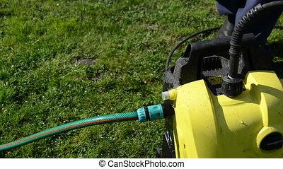 man hose attach - Close of man hand detach water hose to...