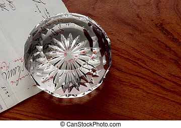 Desktop still life - Cut crystal paperweight sits on...