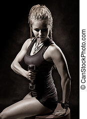 A young girl with dreadlocks training with dumbbells....
