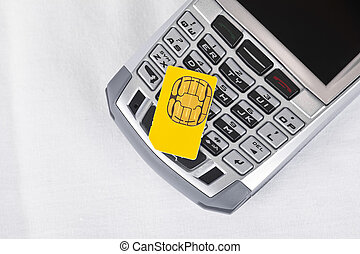 Sim Card - Sim card on top of a cell phone.