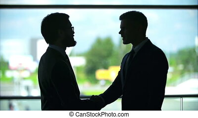 Grey Suits - Outlines of two businessmen shaking hands near...