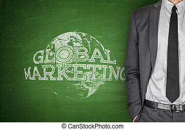 Global marketing concept on blackboard with businessman