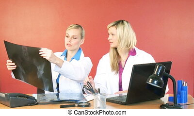 Beautiful doctors studying an x-ray in office - Blonde young...