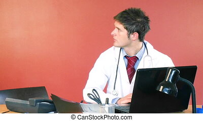 Male and female doctors speaking in hospital office -...