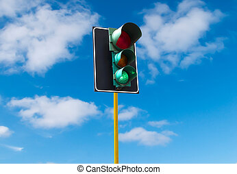 Traffic lights against the sky is lit green