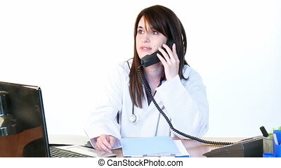 Brunette doctor on phone and using a laptop in office -...