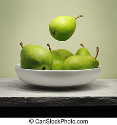 Levitation - Green pear hovering over a bowl - still life