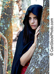 beautiful fantasy woman wit black hood in the woods -...