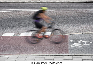 Cyclist in blurred motion on bicycle path on asphalt road