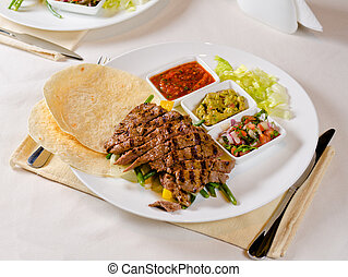 Grilled Steak Fajitas on Plate with Individual Sauces and...