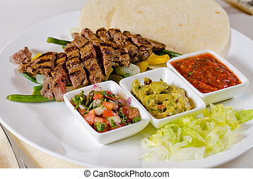 Steak Fajitas on Plate with Tortillas and Individual Sauces