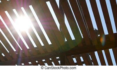 The sun shines through a fence.