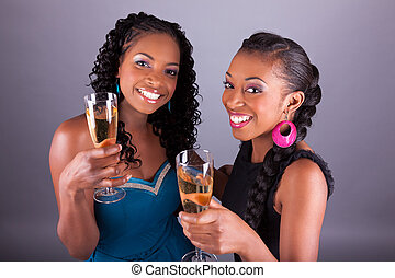 Young beautiful African womans holding a glass of champagne...