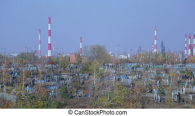 Cemetery on the background of an oil refinery, symbolic...