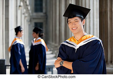 Graduates in Hallway - A young graduate stands in hallway as...