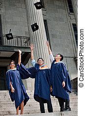 Graduates Hat Toss - A group of graduates toss their mortar...