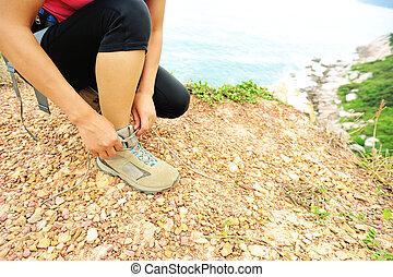 young woman hiker tying shoelaces - young woman hiker tying...
