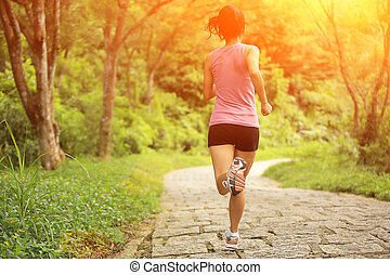 young woman running at forest trail