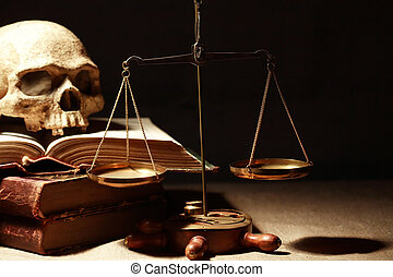 Scales Of Justice - Human skull on old books near weight...