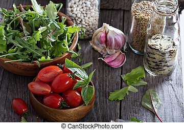 Tomatoes, salad leaves, beans and rice on a wooden table