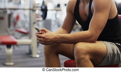 young man with smartphone computer in gym - sport,...