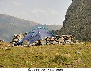 Alpine tent and windbreak from rocks in Carpathians...