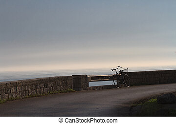 Old bicycle forgot on the waterfront Early morning fog