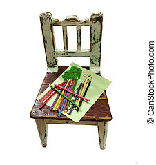 OLD CHILD\'S CHAIR WITH PAPER AND PENCILS ON THE SEAT