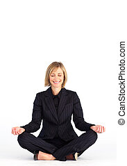 Mature businesswoman doing meditation exercises on the floor