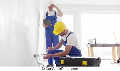 smiling builders with tablet pc and equipment - building,...