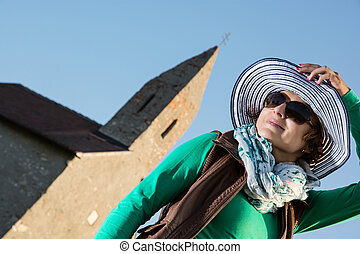 Young brunette with stylish hat and old romanesque church