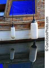 Two fender on an old boat with reflection in water - Two...