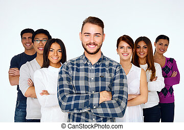 Portrait of happy young casual people with arms folded over...