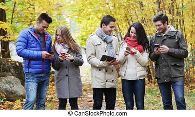 smiling friends with smartphones and tablet pc - season,...