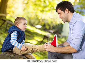Father and son in nature - Father is helping his son to tie...
